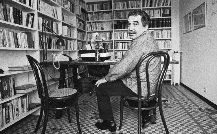 Gabriel Garcia Marquez sentando delante de muchos libros