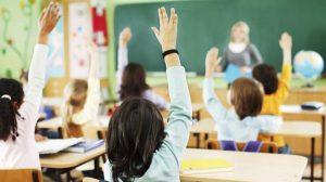 Alumnos levantando la mano en el colegio